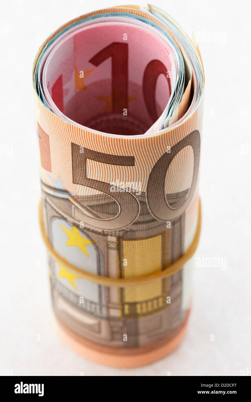 50 Euro note on a money roll of Euros rolled up with an elastic band on a white background to illustrate saving - Stock Image
