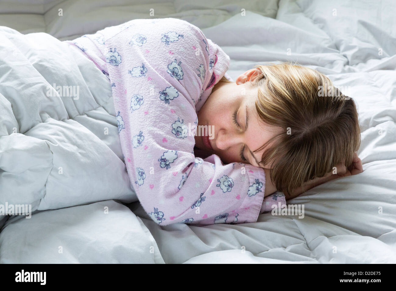 young woman asleep in bed - Stock Image
