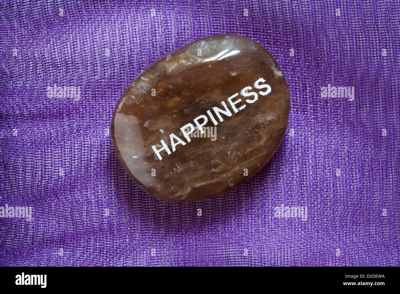 Fair Trade sentiment pebbles - Happiness pebble isolated on purple background - Stock Image