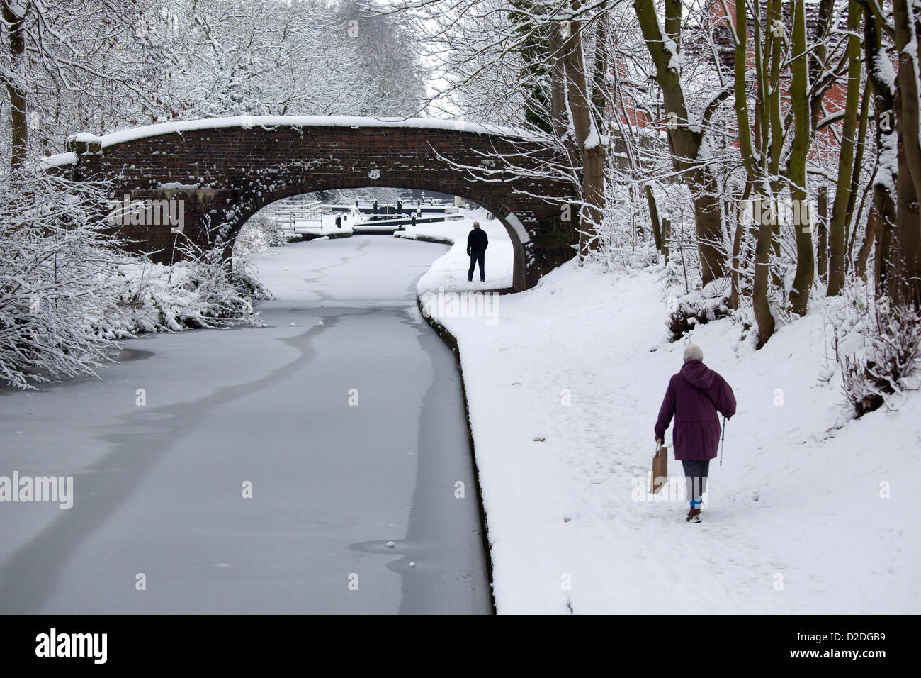 People walking along a frozen Coventry canal in Atherstone, North Warwickshire. - Stock Image