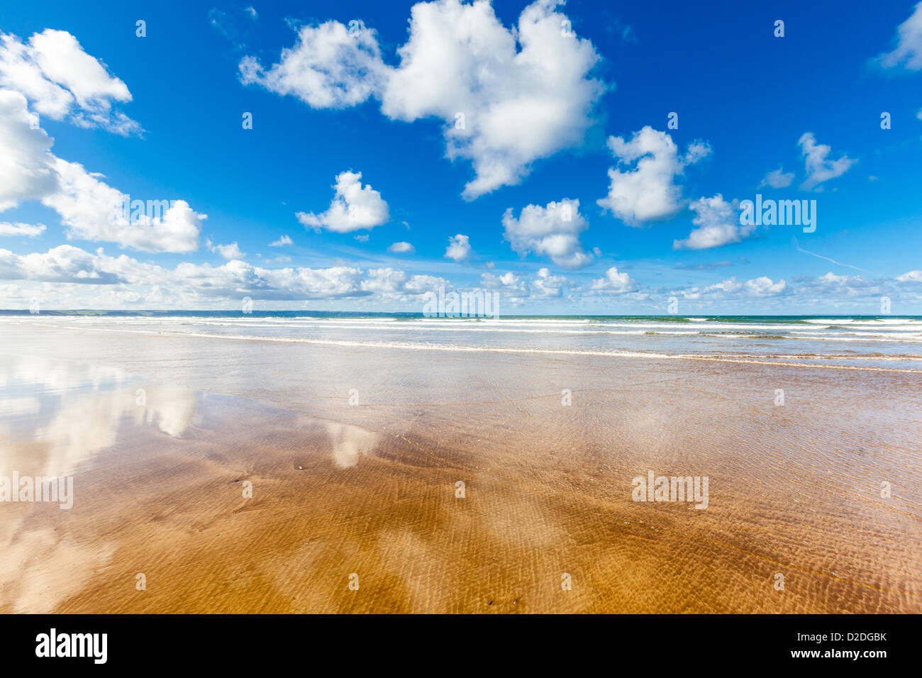 Empty beach with fluffy clouds reflected in the wet sand, Saunton Sands in North Devon, UK. - Stock Image