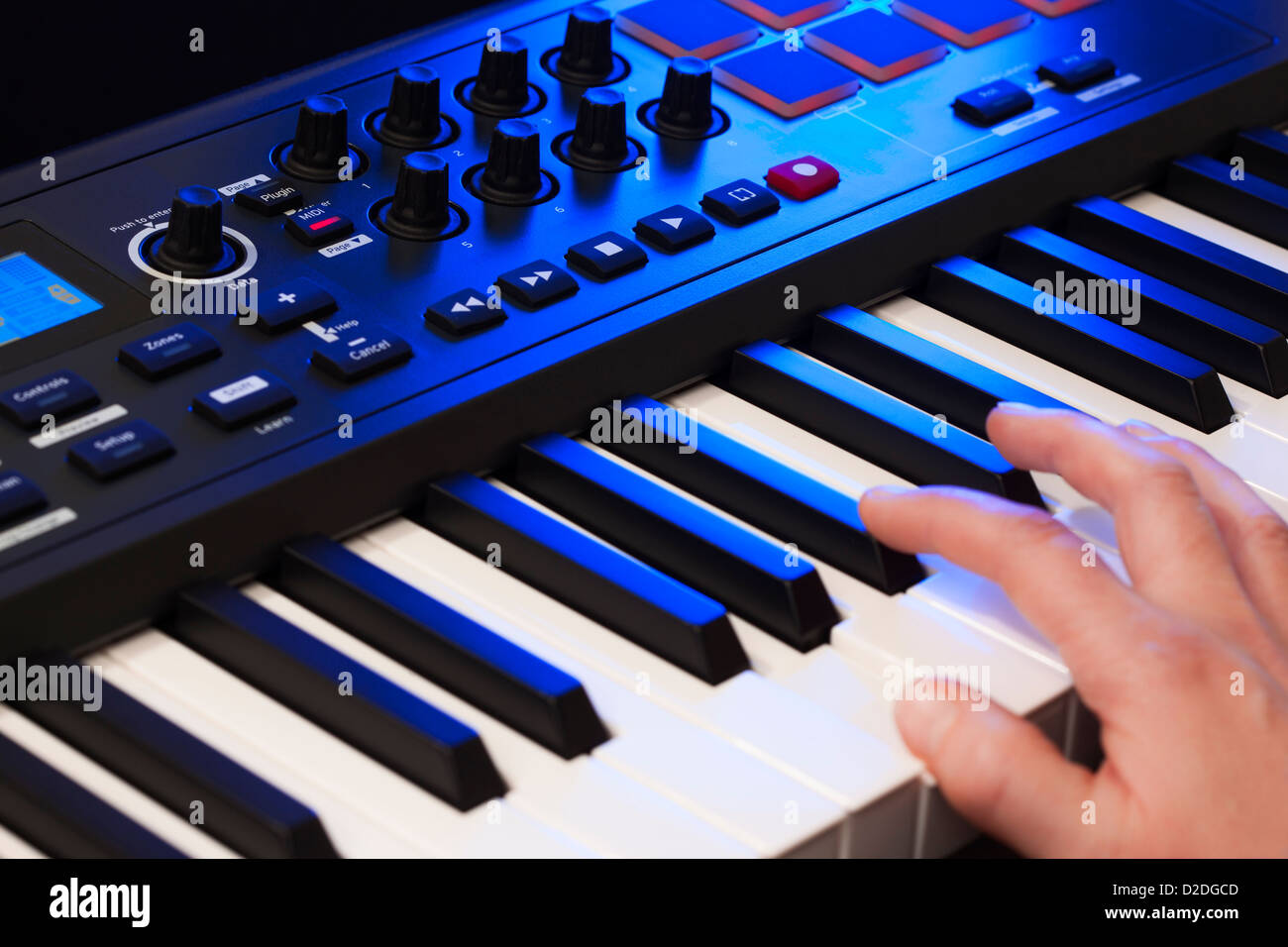 Close up of a hand playing a MIDI controller keyboard. - Stock Image
