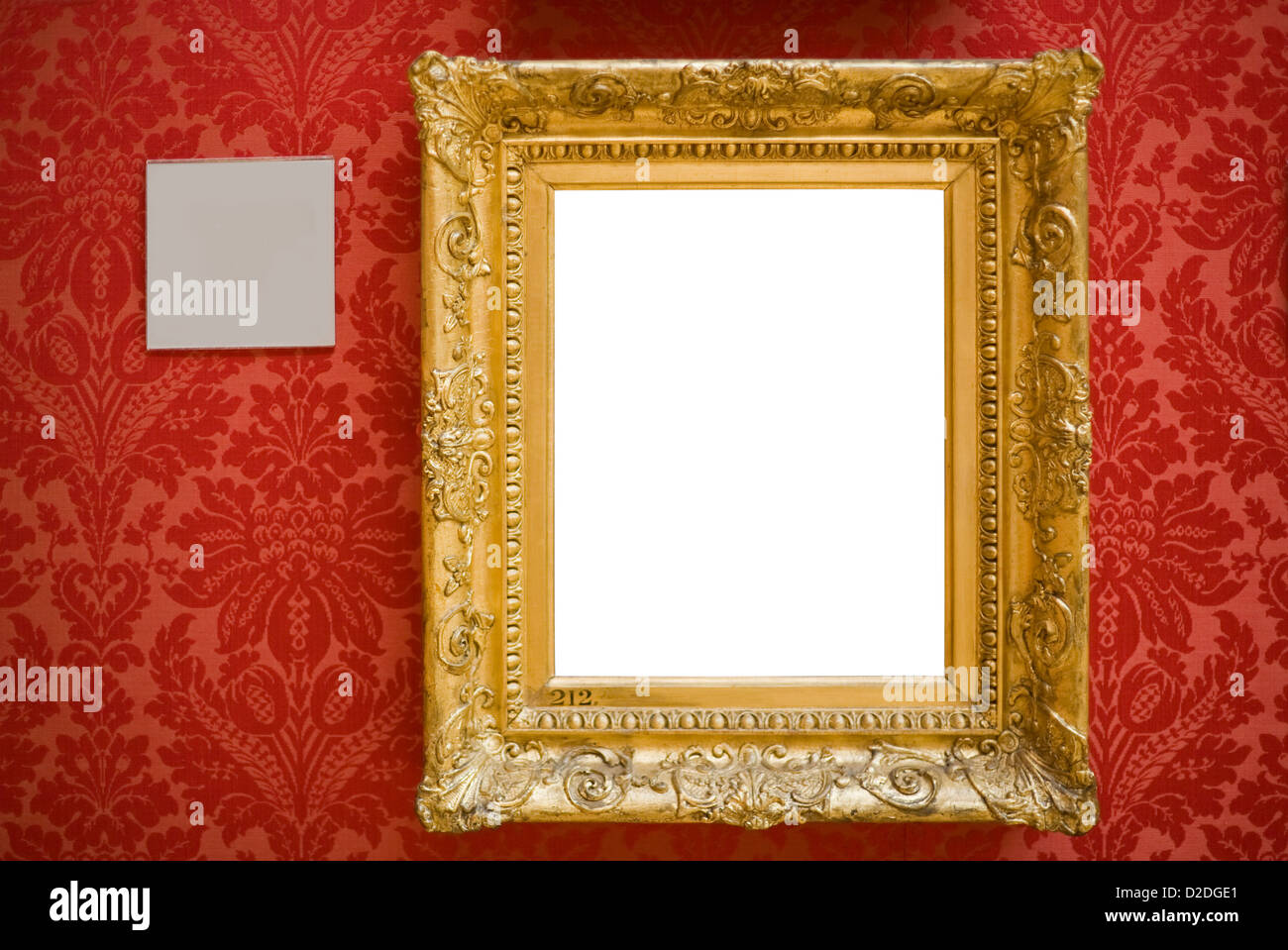 Ornate gold frame hanging on an art gallery wall, accompanied by a blank description label. - Stock Image