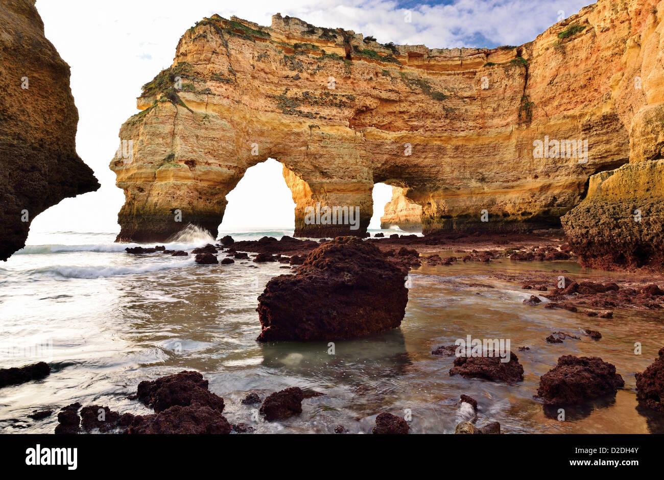 Portugal, Algarve: Limestone arcs with ebb tide at beach Praia da Marinha - Stock Image