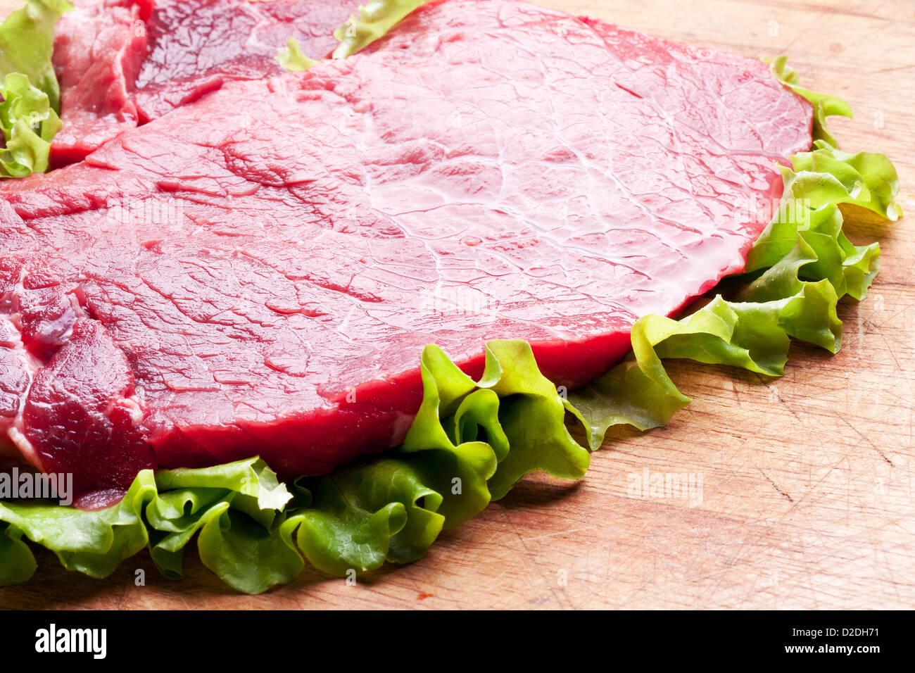 Raw meat on lettuce leaves. Wooden background. - Stock Image