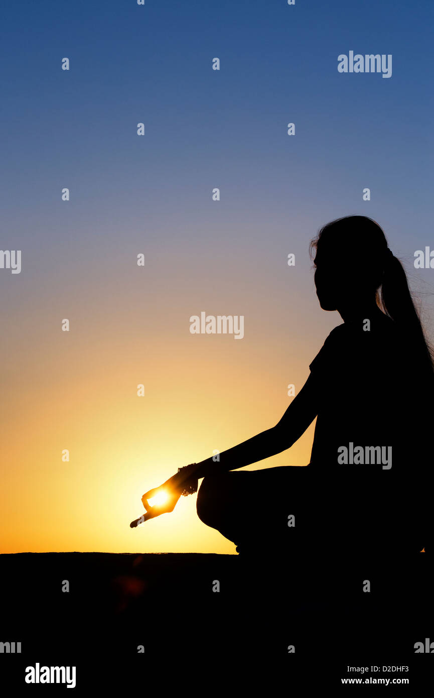 Sunset silhouette of an Indian girl meditating. Andhra Pradesh, India - Stock Image