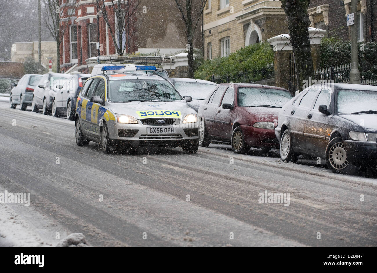 A Police car drives down a road covered in snow and slush in Brighton, East Sussex, England, United Kingdom. UK - Stock Image