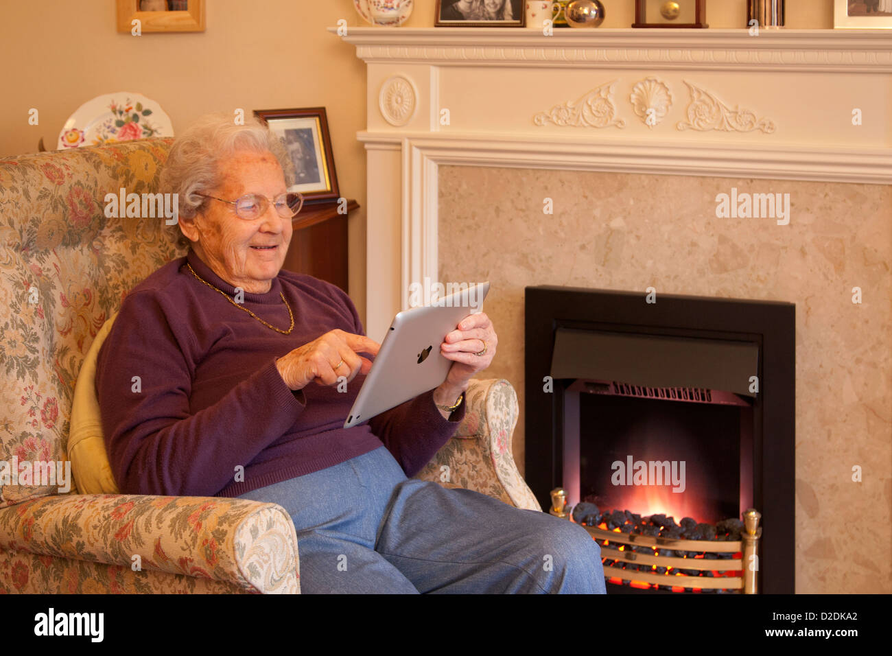 Elderly woman pensioner with glasses on apple ipad tablet at home relaxing on chair playing computer game - Stock Image