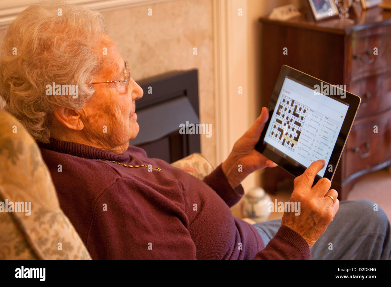 Elderly woman pensioner with glasses on apple ipad tablet at home relaxing and doing a newspaper crossword on-line - Stock Image