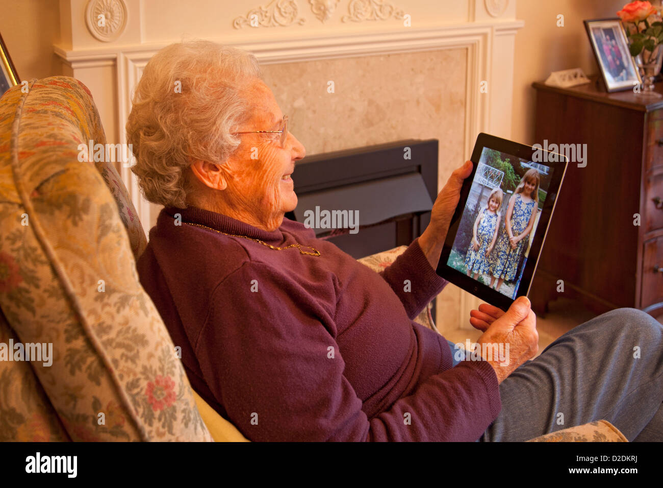 Elderly woman pensioner with glasses on apple ipad tablet at home relaxing on chair looking at photographs of grandchildren - Stock Image
