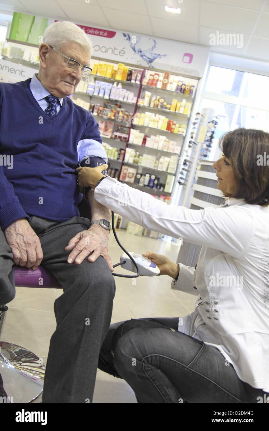 France, drugstore, pharmacist checking client's bloodpressure - Stock Image