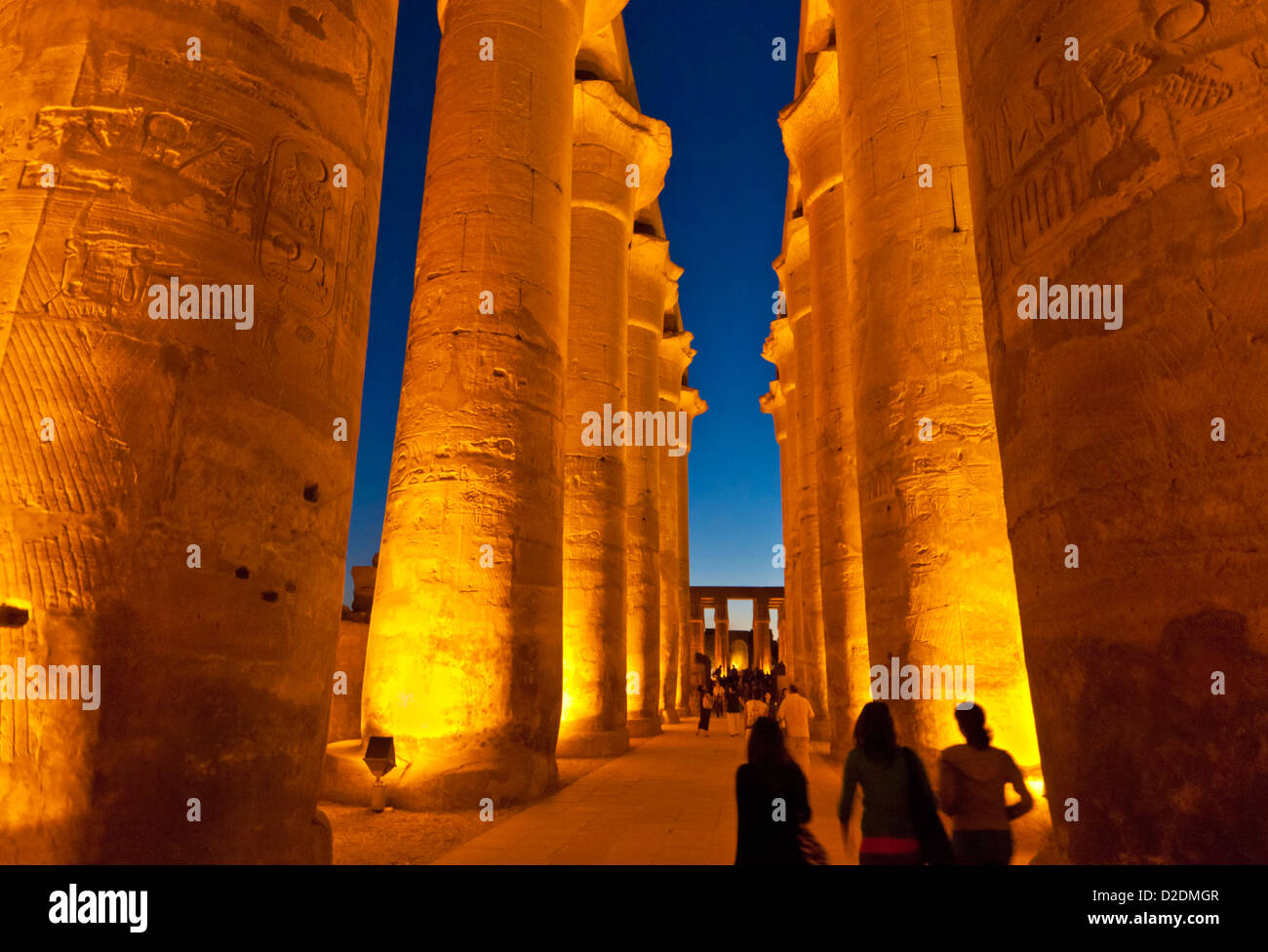 Tourists walking among the Floodlit columns of the court of Amenhotep III  Temple of Luxor at sunset Luxor Egypt - Stock Image