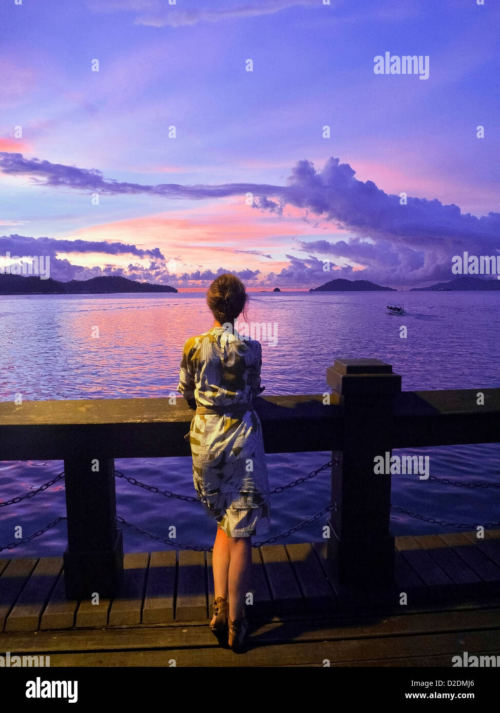 Malaysia, Borneo, Kota Kinabalu, South China Sea, Young woman watching the sunset - Stock Image