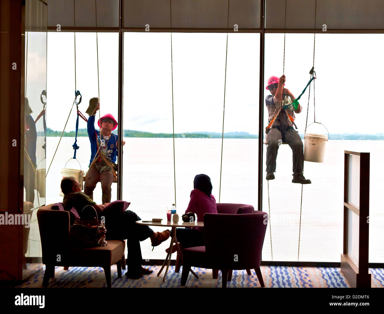 Malaysia, Borneo, Kota Kinabalu, Four Points Hotel, People in a sitting room, Window cleaners in the background - Stock Image