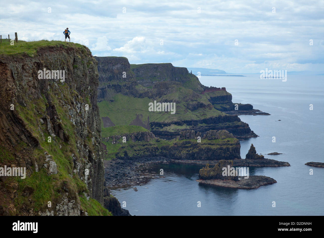 Walker on top of Benbane Head, on the Causeway Coast Way walking trail, County Antrim, Northern Ireland. Stock Photo