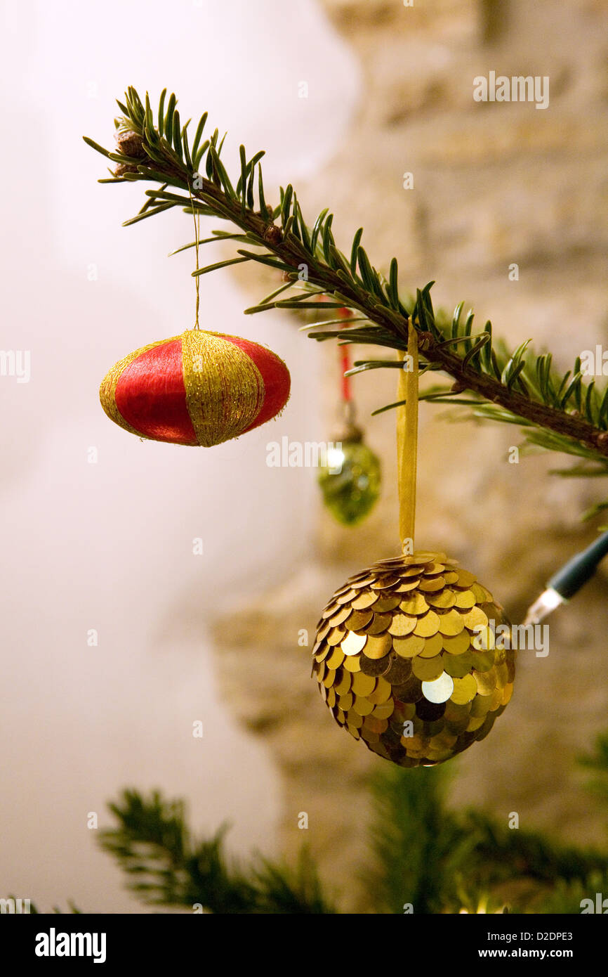 Vintage fabric and glass Christmas decorations hanging on a Nordmann Fir (Abies nordmanniana) Christmas tree. Stock Photo