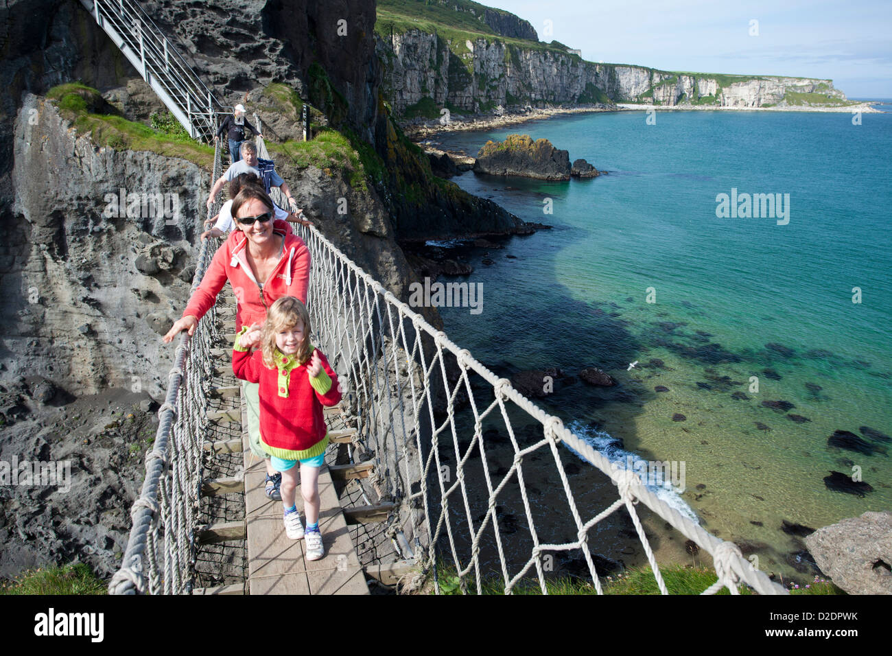 Woman and child crossing Carrick-a-rede Rope Bridge, County Antrim, Northern Ireland. - Stock Image