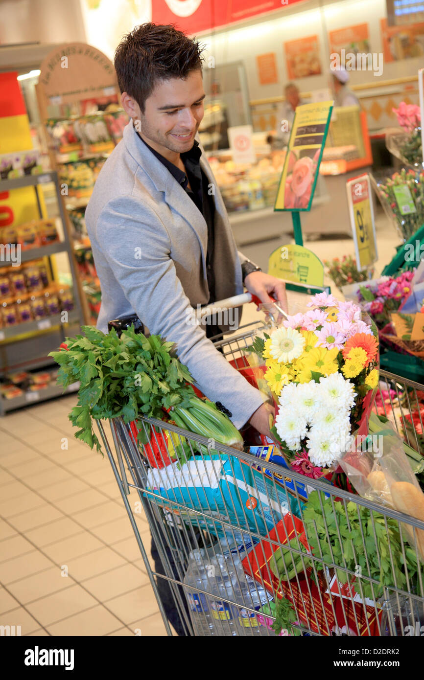 France, supermarket, customer and flowers. - Stock Image