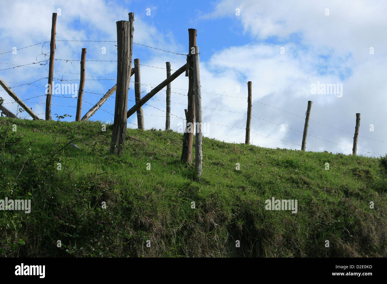 A barbed wire fence stretching over a hill in  a farmers pasture in Cotacachi, Ecuador - Stock Image