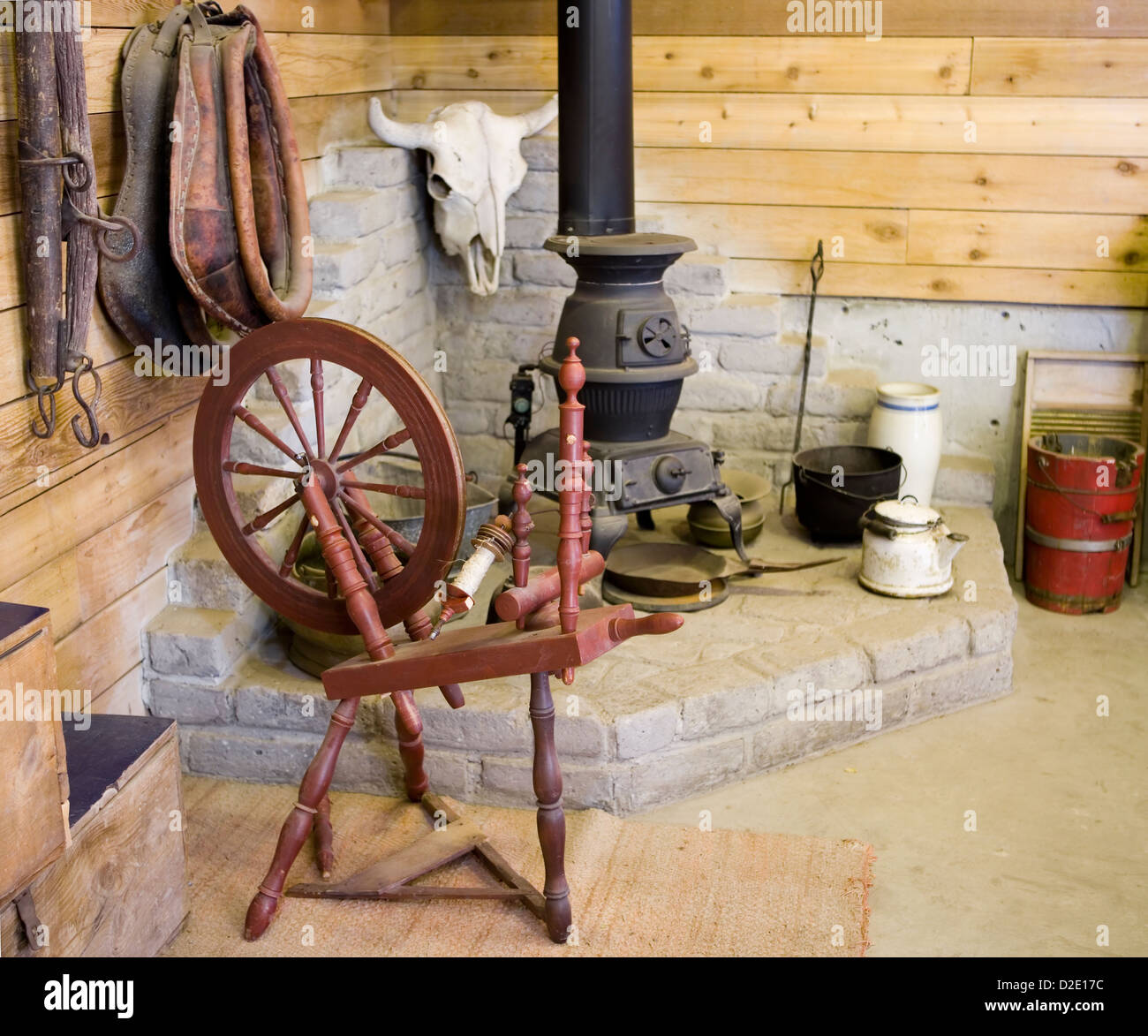 Spinning wheel, potbelly stove and other antiques - Stock Image