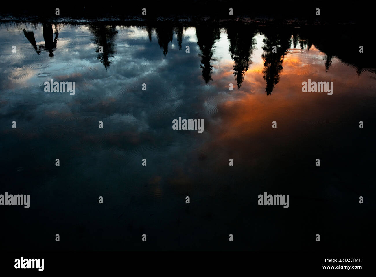 One man reflected upside down in a lake with colorful clouds and rain drops. - Stock Image