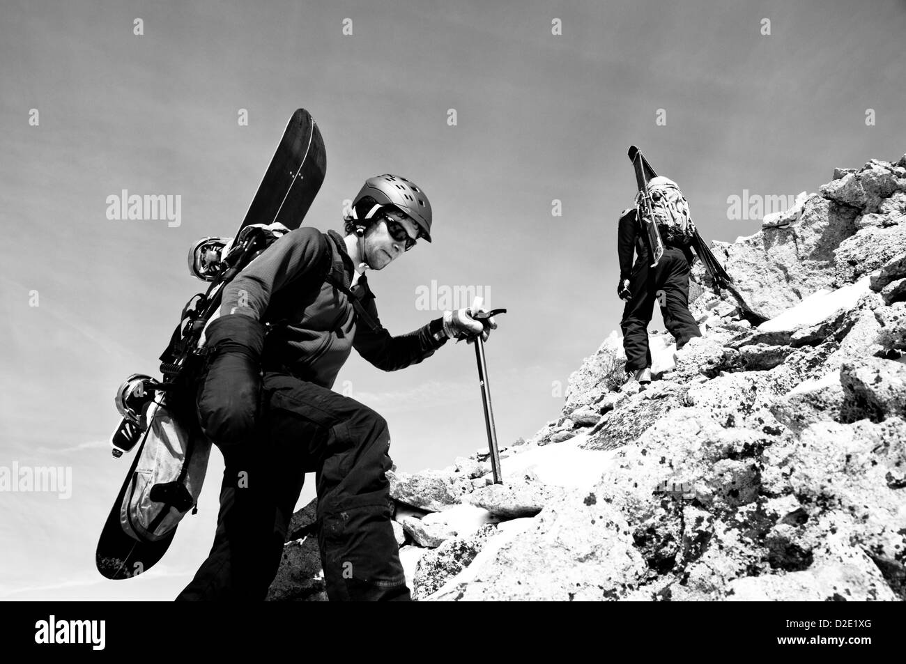 Snowboarder Climbing up a rocky ridge to ride down. - Stock Image