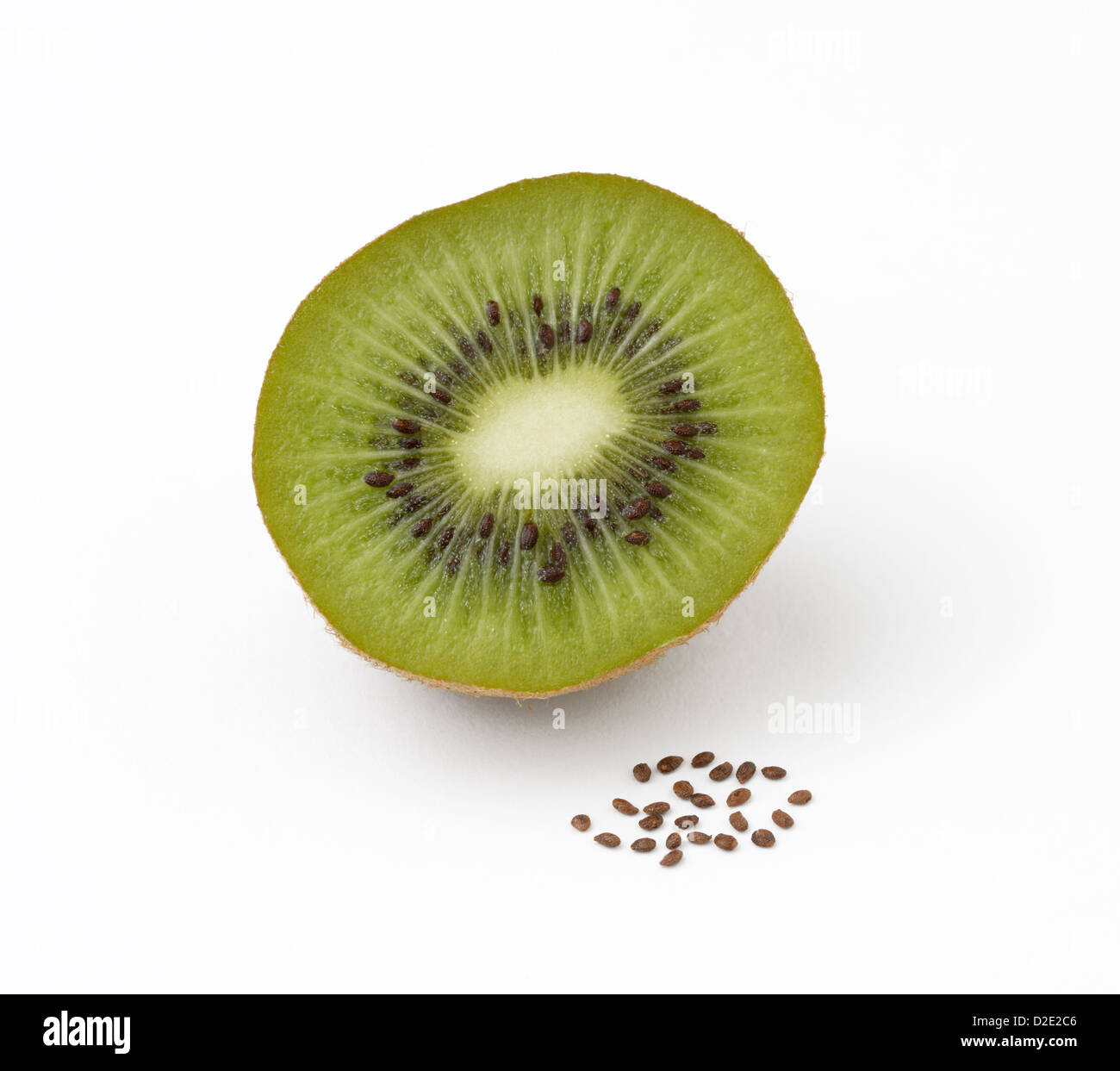 Kiwifruit, Actinidia deliciosoa, sliced open showing the seeds inside and with a pile of seeds in front - Stock Image