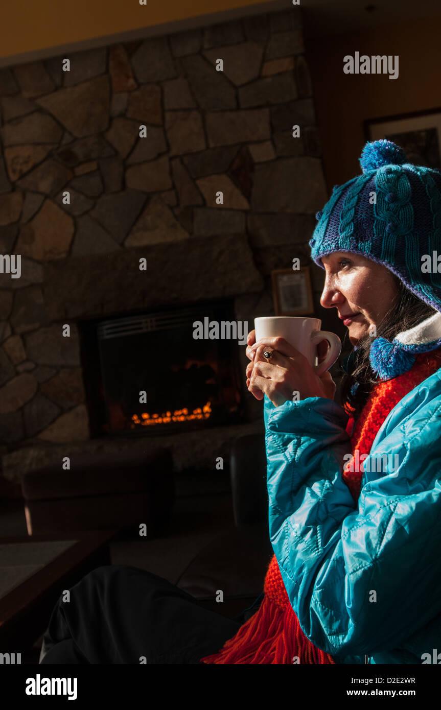 Woman enjoying a mug of hot chocolate near a fireplace in lodge in Crawford Notch, NH. - Stock Image