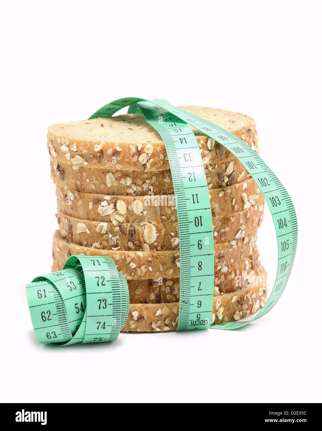 Fresh multigrain bread tied by green measuring tape - diet doncept. - Stock Image