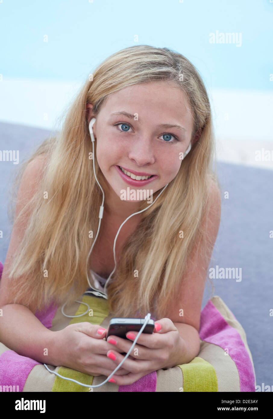 Attractive smiling 13 years old teenage girl in poolside holiday environment using  Apple iPhone smartphone wearing - Stock Image
