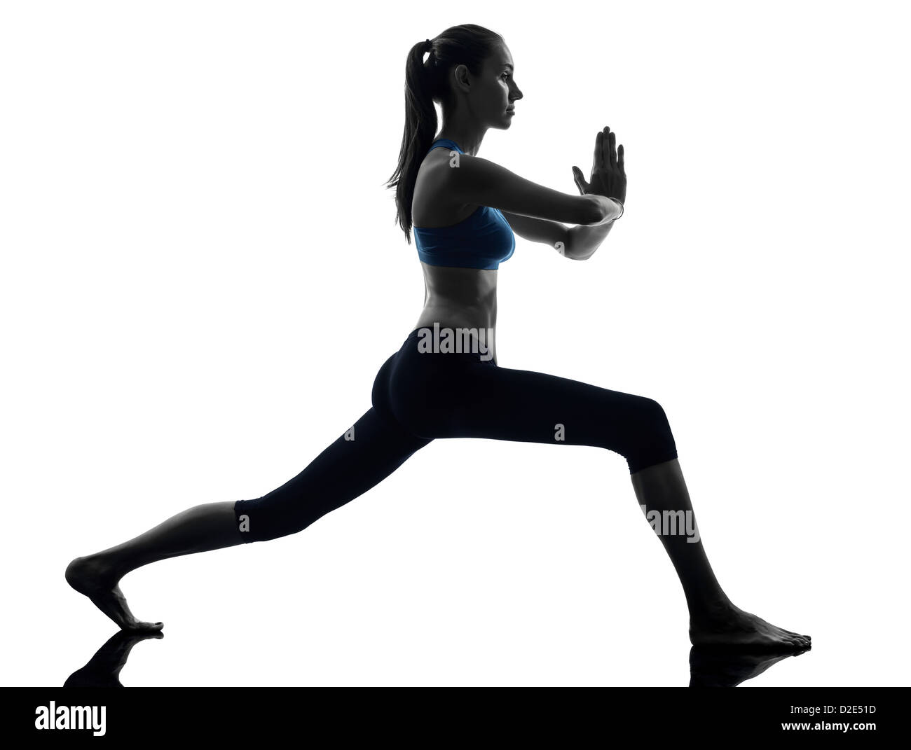 one  woman exercising yoga warrior position in silhouette studio isolated on white background - Stock Image