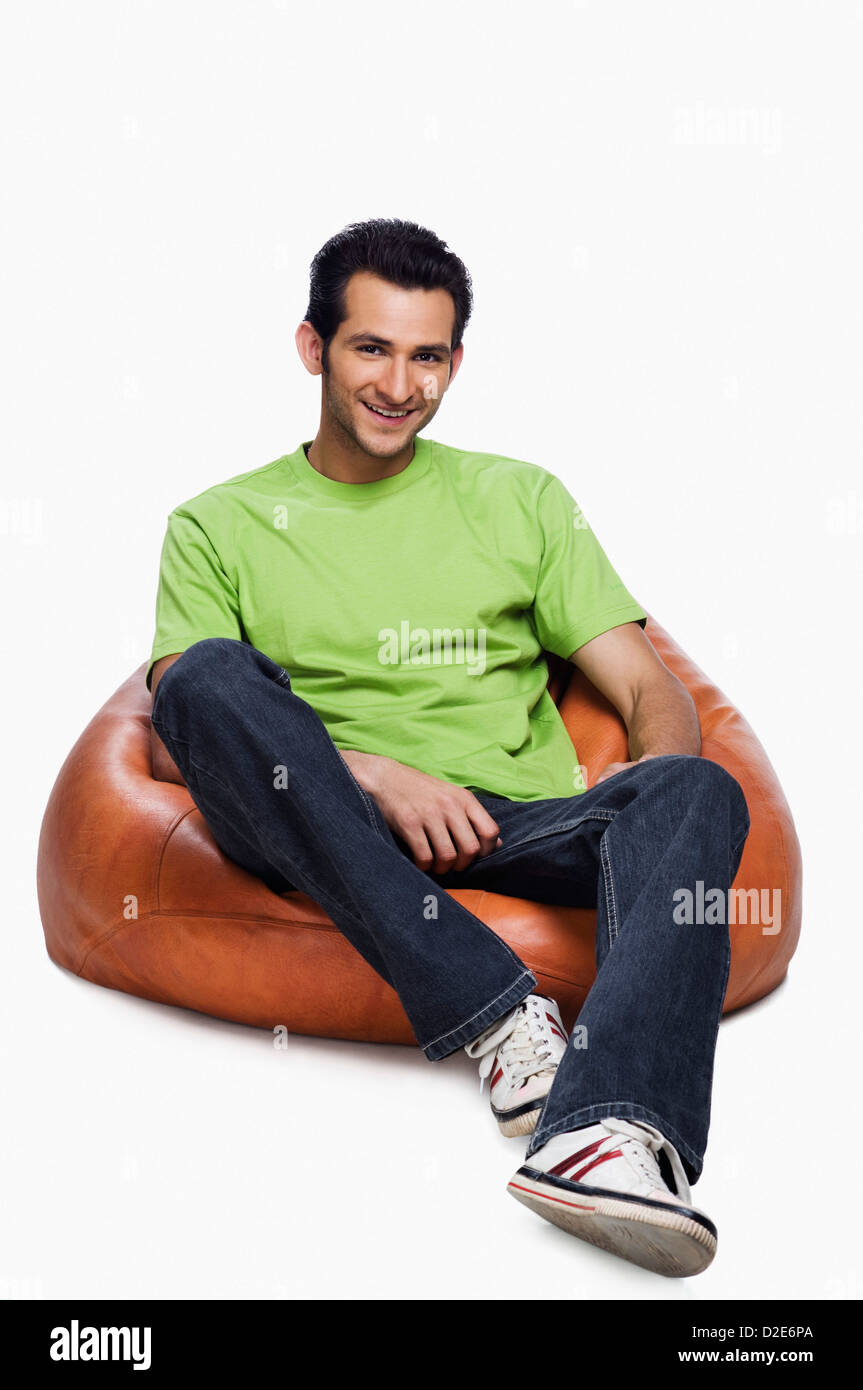 Portrait of a man sitting on a bean bag and smiling - Stock Image