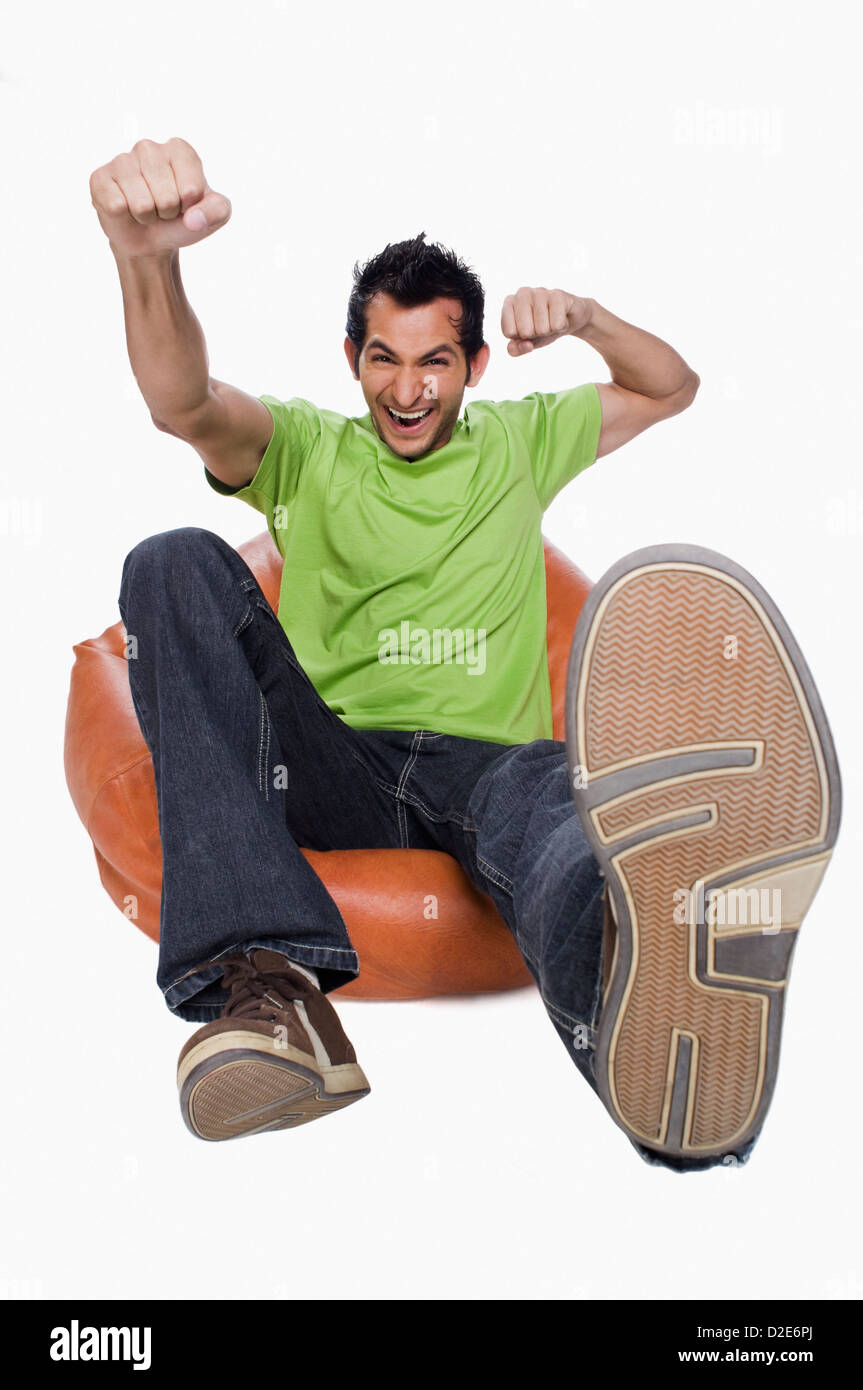 Portrait of a man cheering on a bean bag - Stock Image
