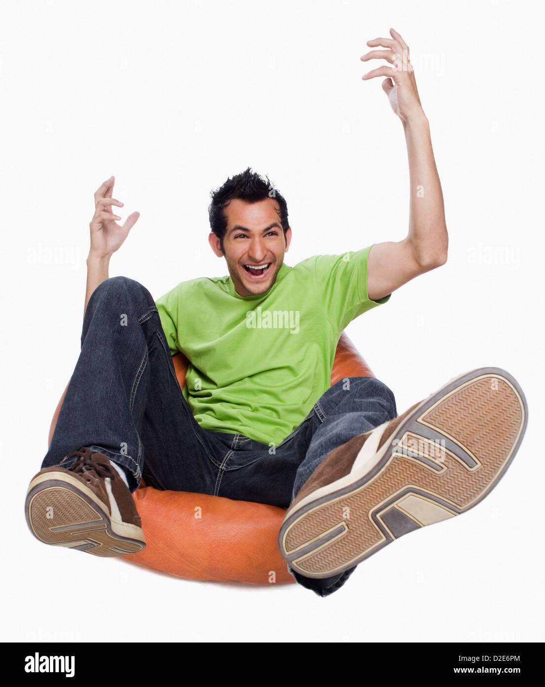 Man cheering on a bean bag - Stock Image
