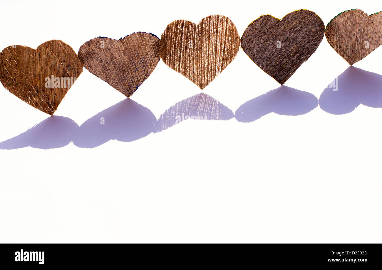 Line of coconut husk bark heart shapes with shadows on white - Stock Image