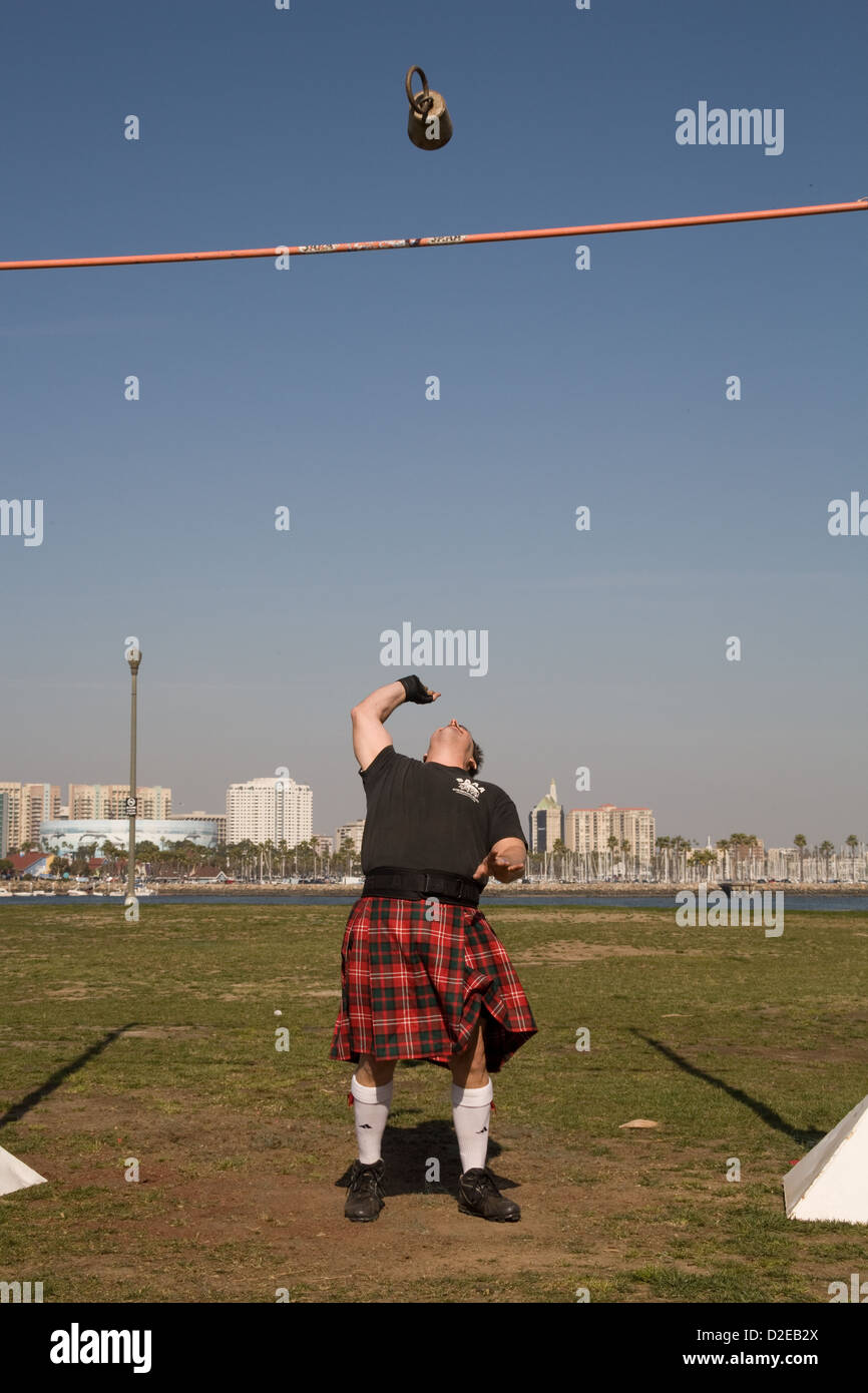 A man in a red kilt throws a weight over the bar at the Queen Mary Scotsfest in Long Beach, CA - Stock Image