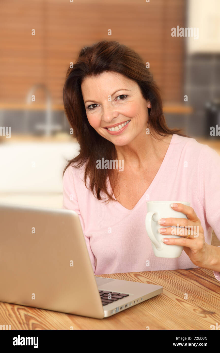 Attractive mature woman using a laptop, sitting at the kitchen table holding a white mug, smiling to camera. Stock Photo