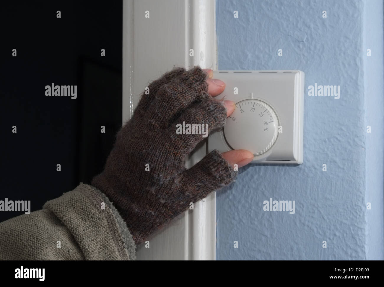 Austerity - turning down temperature on domestic central heating thermostat - Stock Image