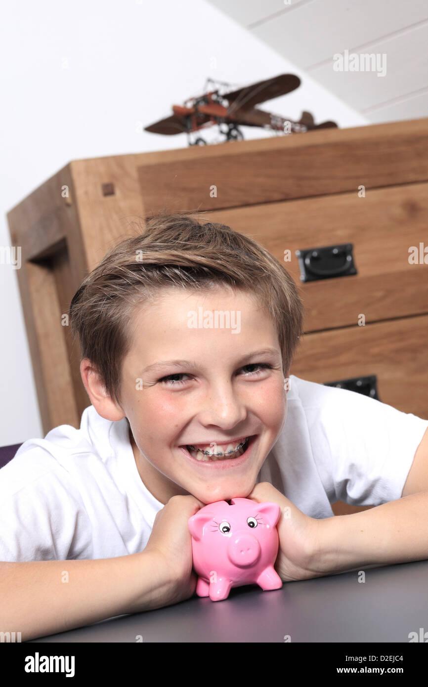 France, boy saving money piggy bank - Stock Image