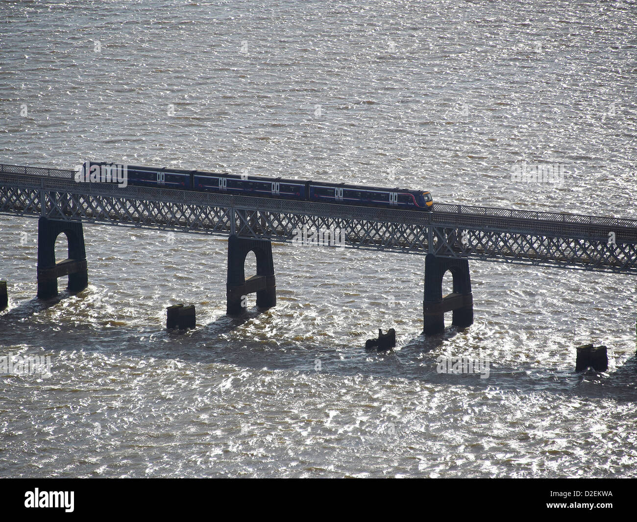 Scotrail Train on the Tay rail bridge, Dundee, Tayside, Scotland, the pillars of the old bridge visible in front - Stock Image