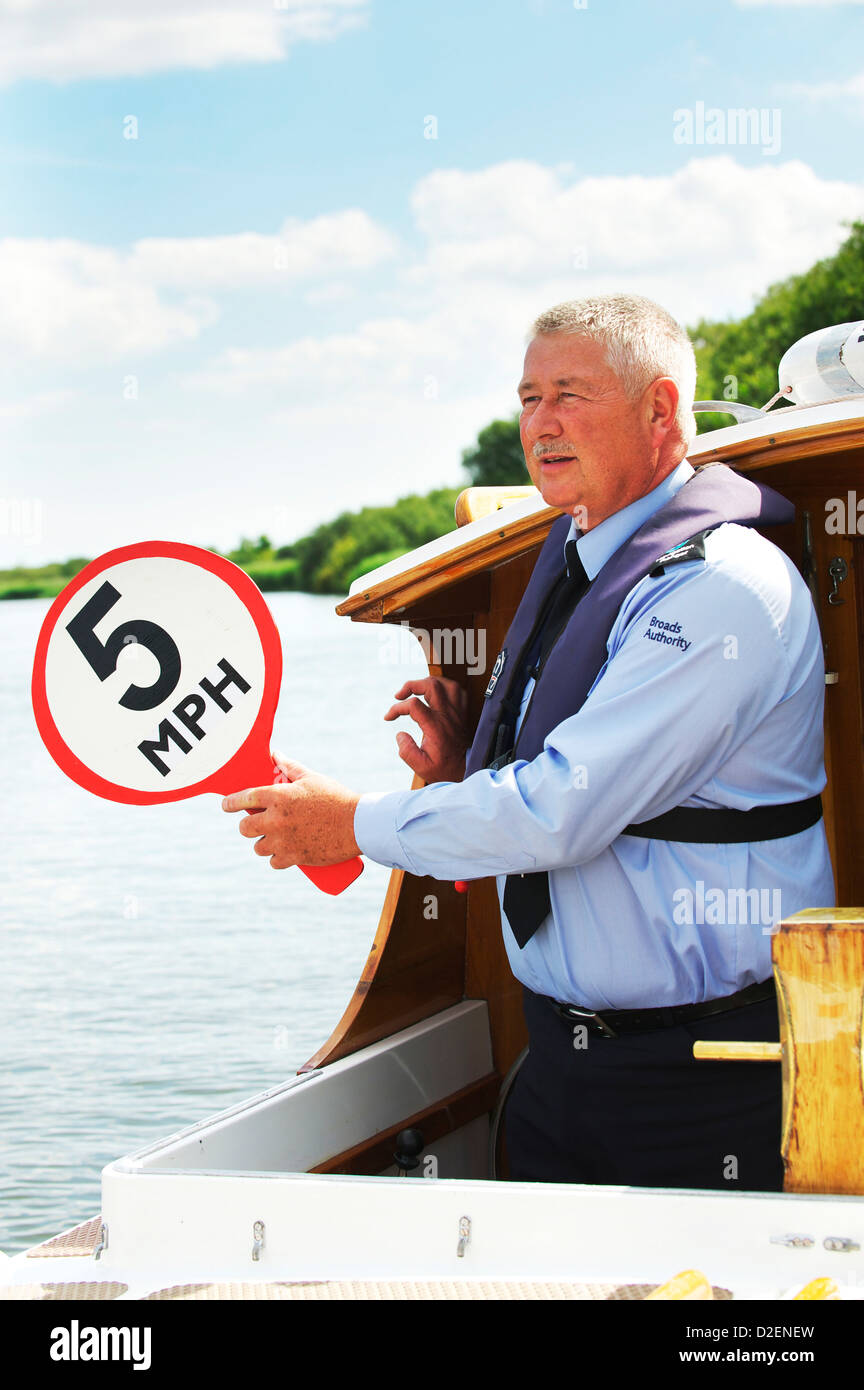 National Parks Broads Authority Police Officer holds out speed limit sign for passing holiday makers on the Norfolk - Stock Image