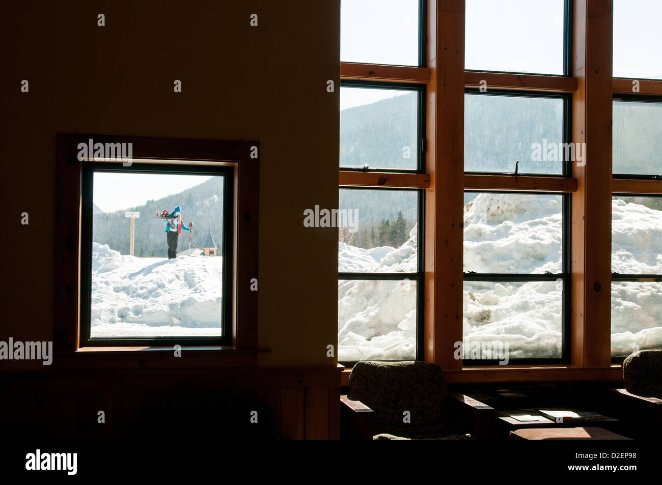 Woman outside the door of a lodge with snowshoes and lots of snow. - Stock Image