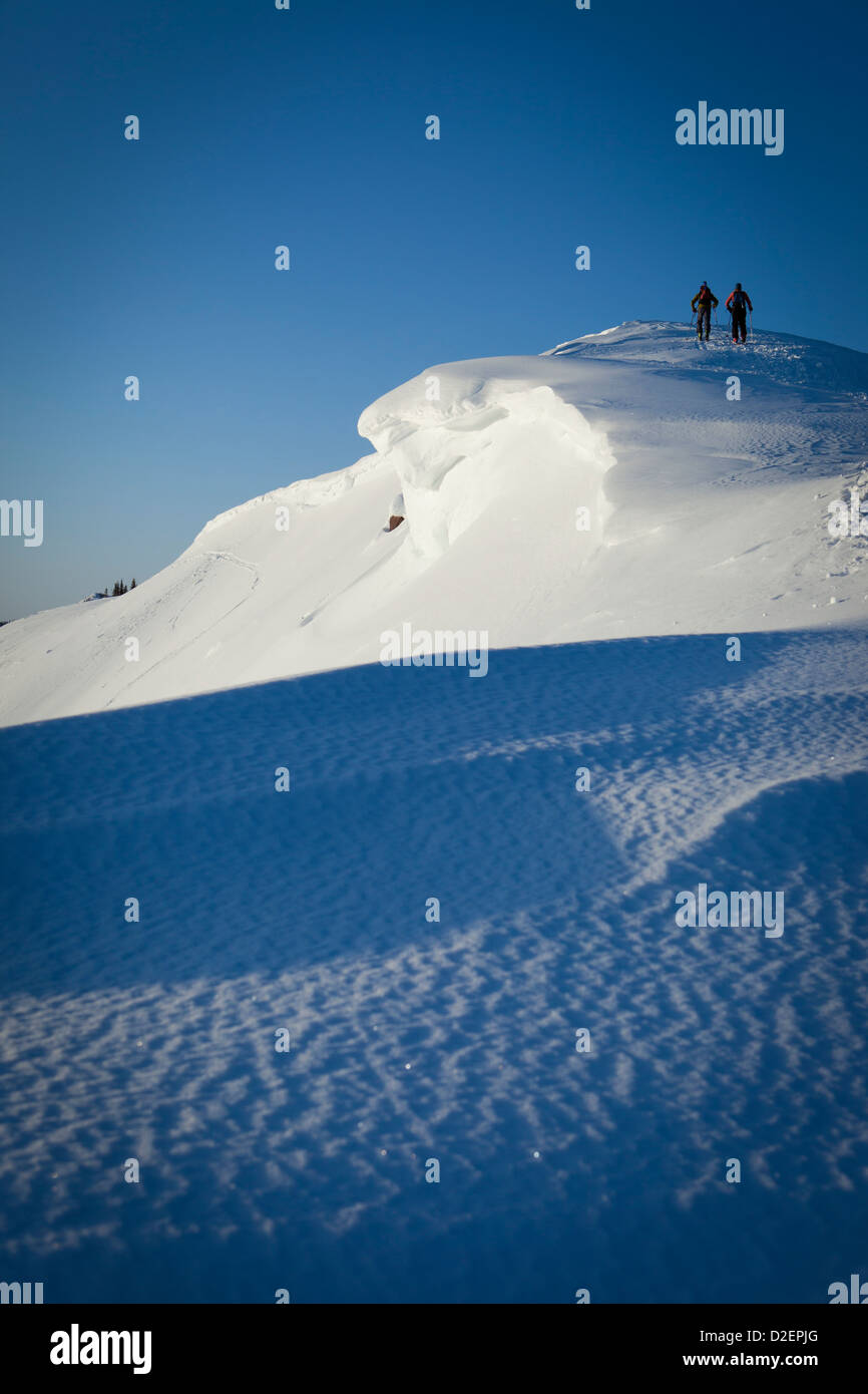Silhouettes of two people backcountry skiing up a mountain at sunrise in purple light. - Stock Image