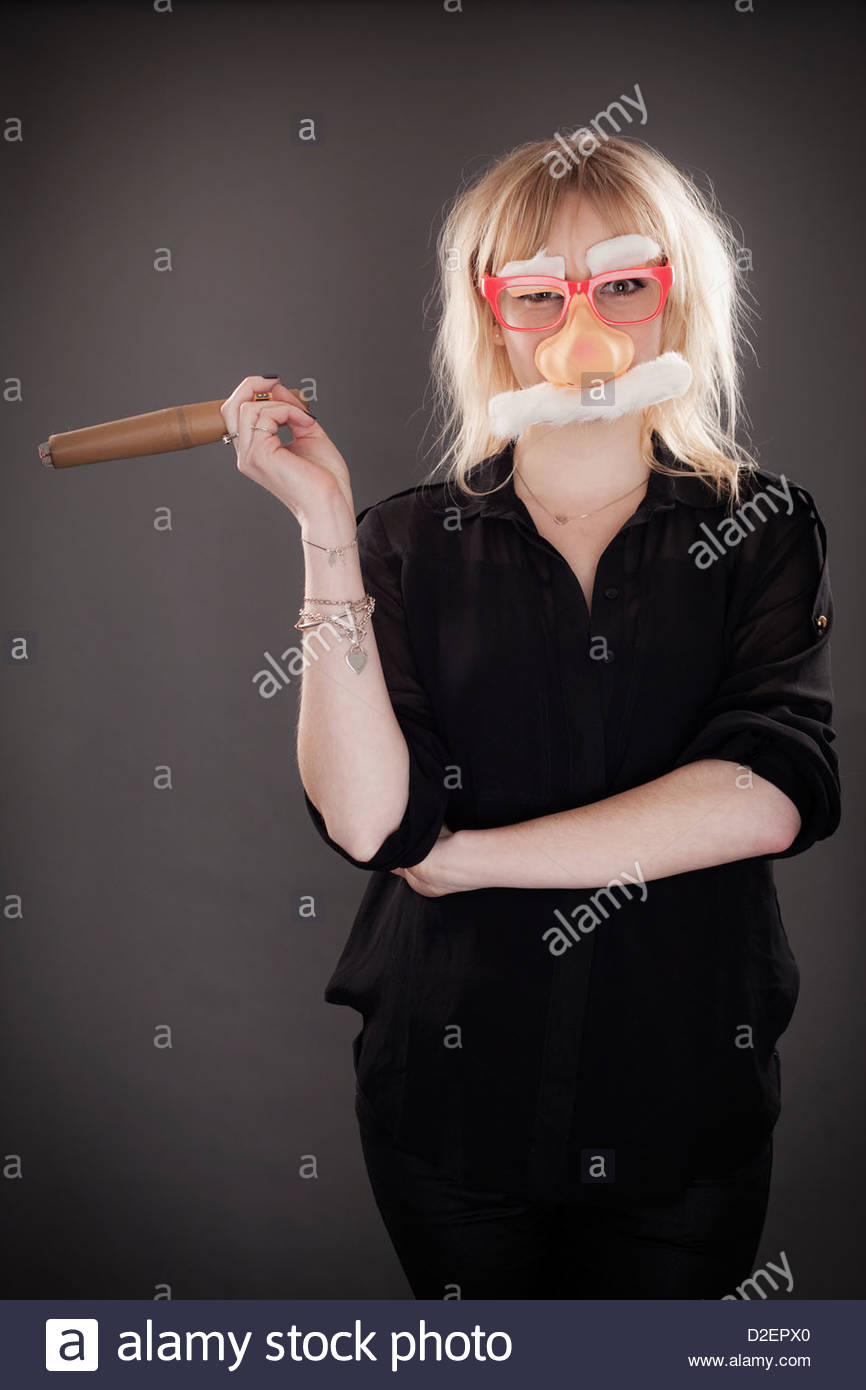 Young woman wearing disguise, studio portrait - Stock Image