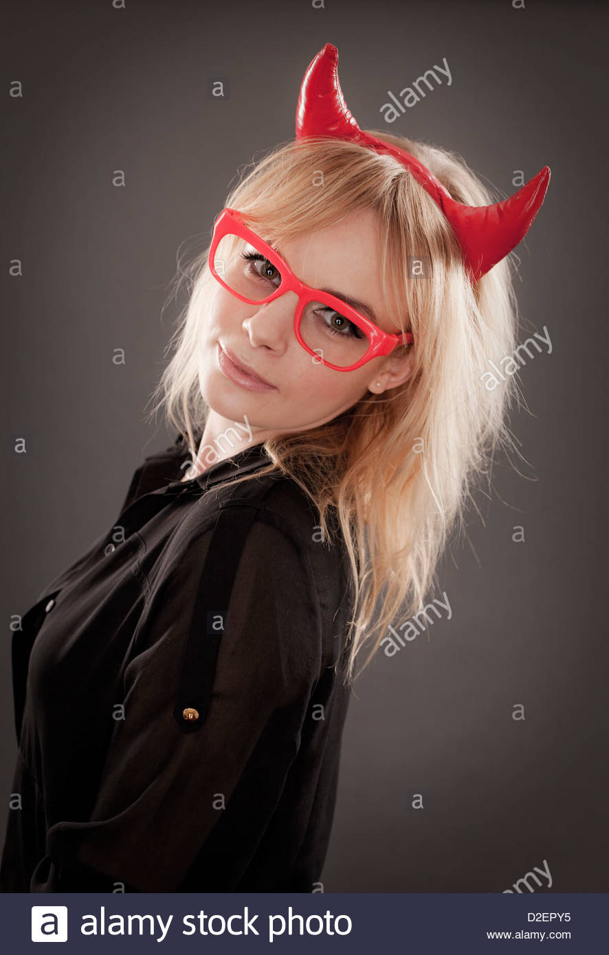Young woman wearing red glasses and devil horns, studio portrait - Stock Image