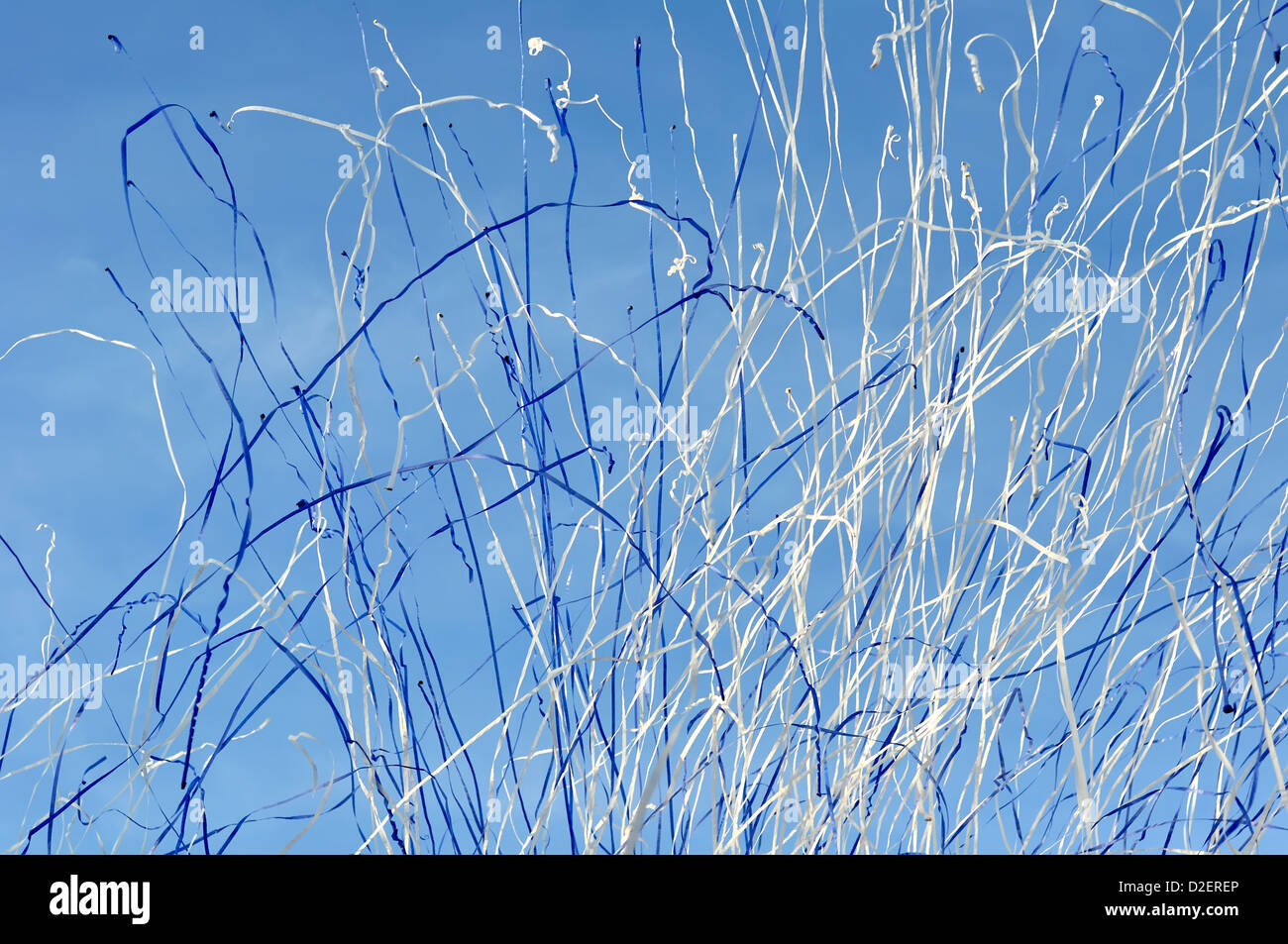 falling blue and white streamers in the city festival - Stock Image