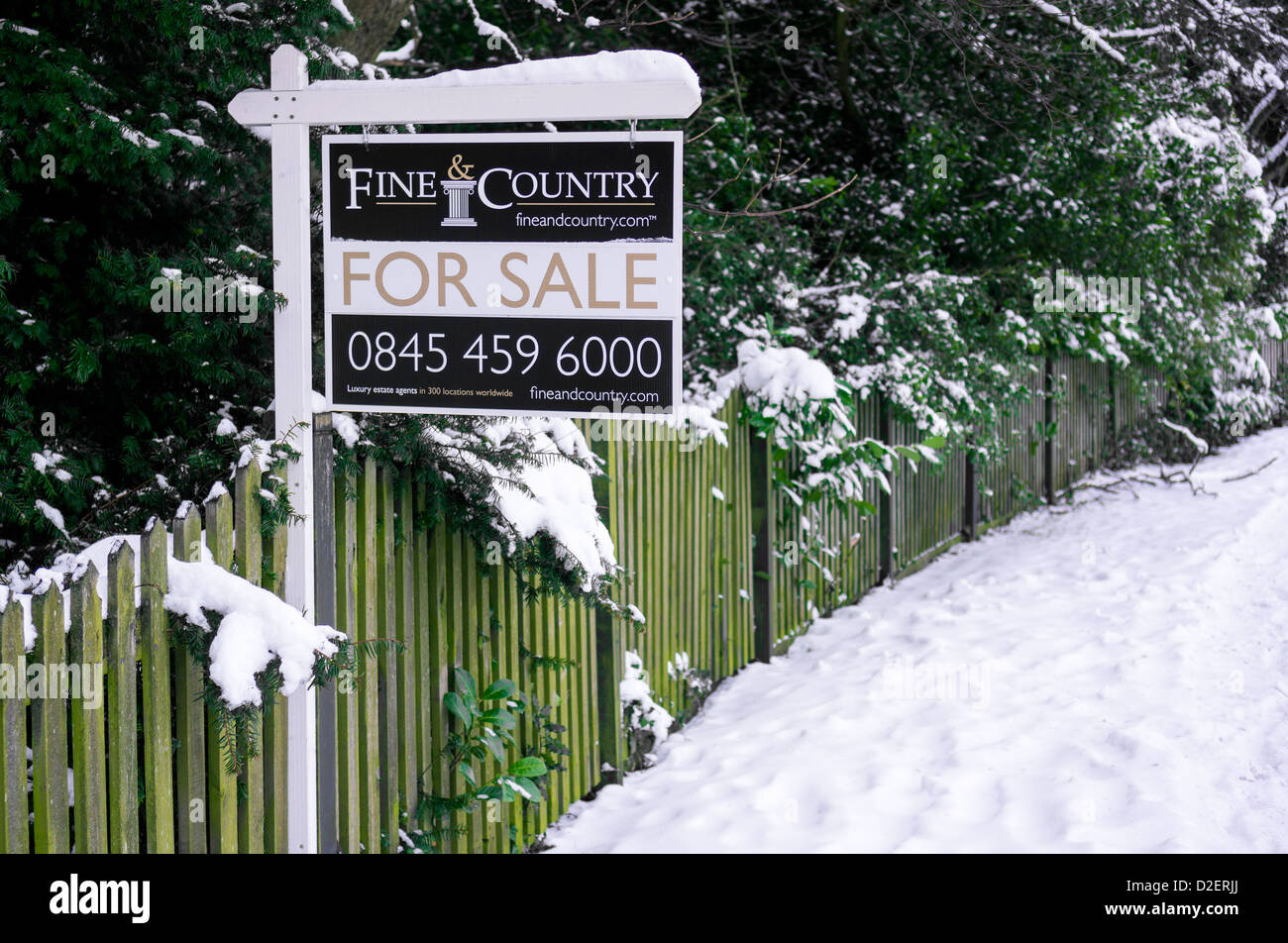 A country house for sale sign in winter. - Stock Image