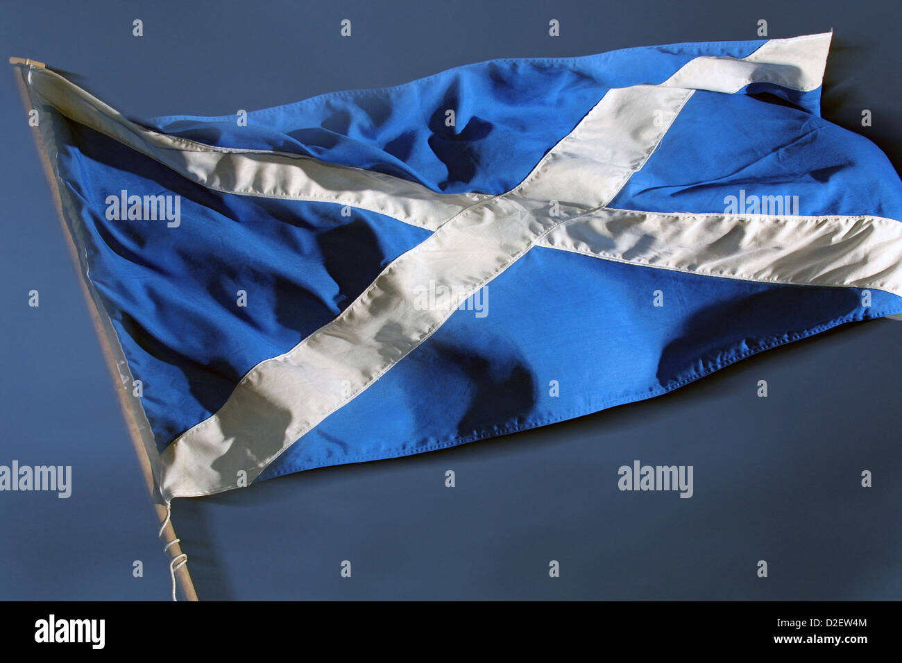 The St. Andrews Cross, the national flag of Scotland, seen against a dark sky - Stock Image