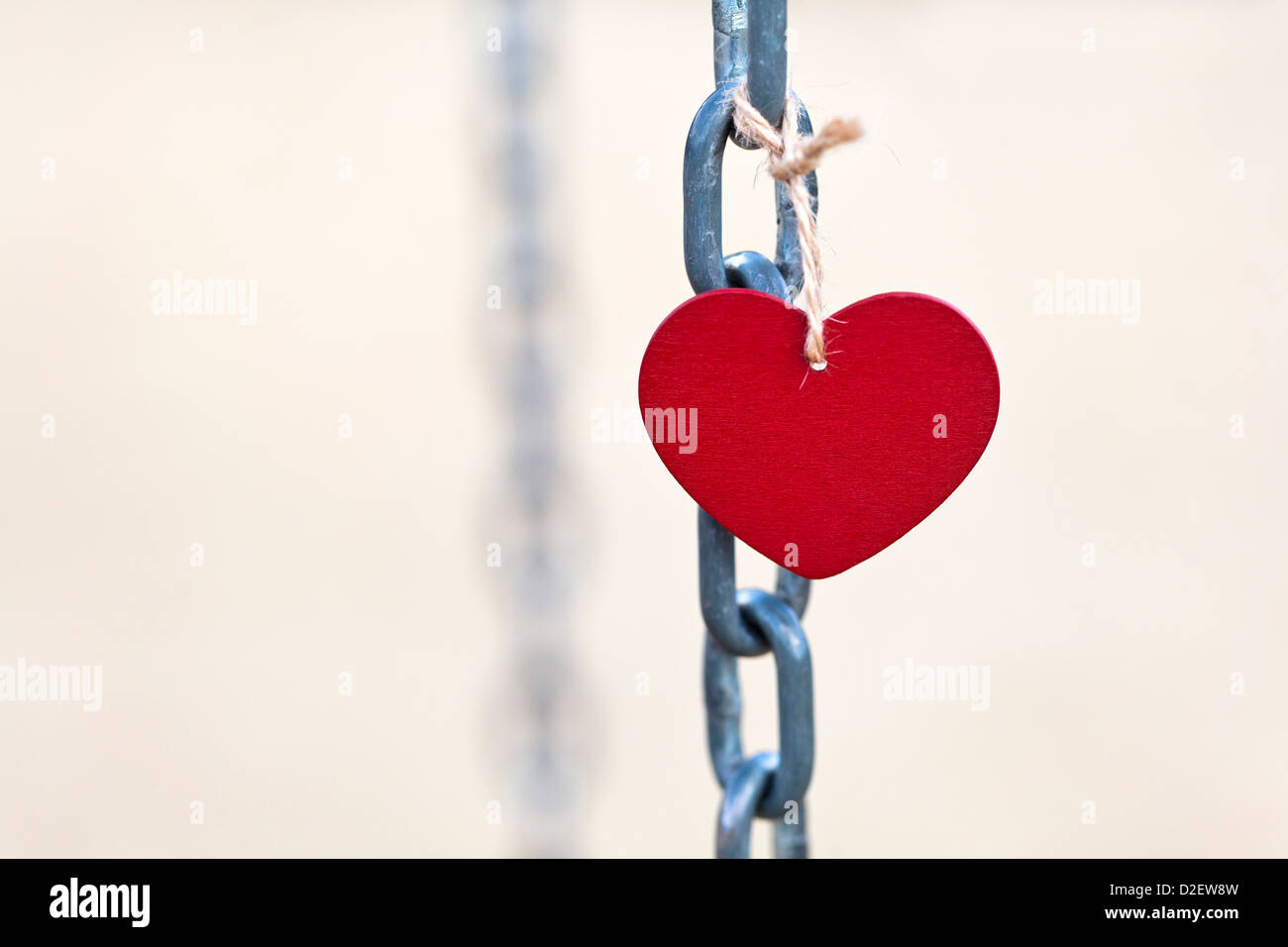 Love shape hangs in a chain. Love concept picture with copy space. Stock Photo