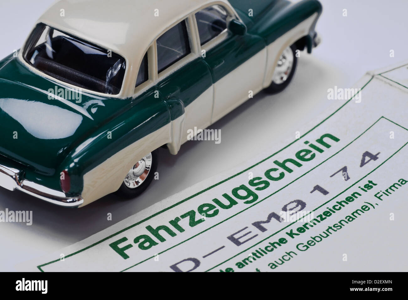 Detail photo of a vehicle registration certificate in German, alongside is a model car - Stock Image